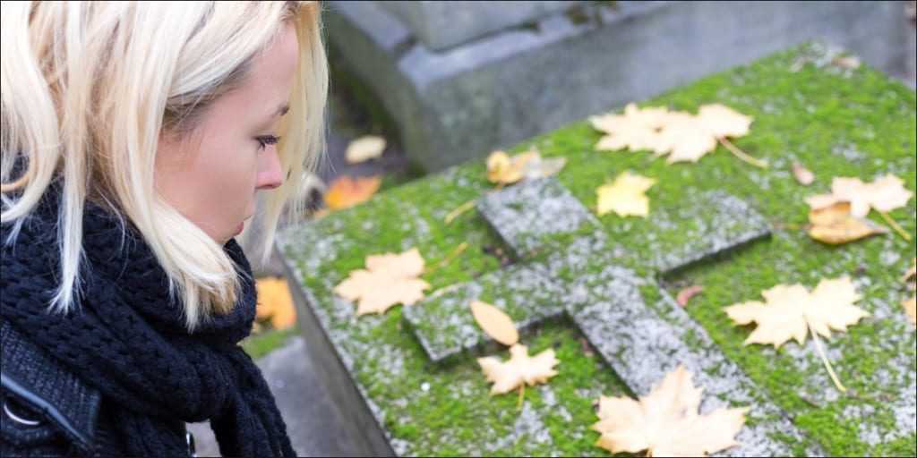 woman standing over grave of wrongful death individual