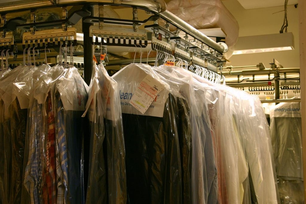 multiple shirts hanging from a dry cleaning line