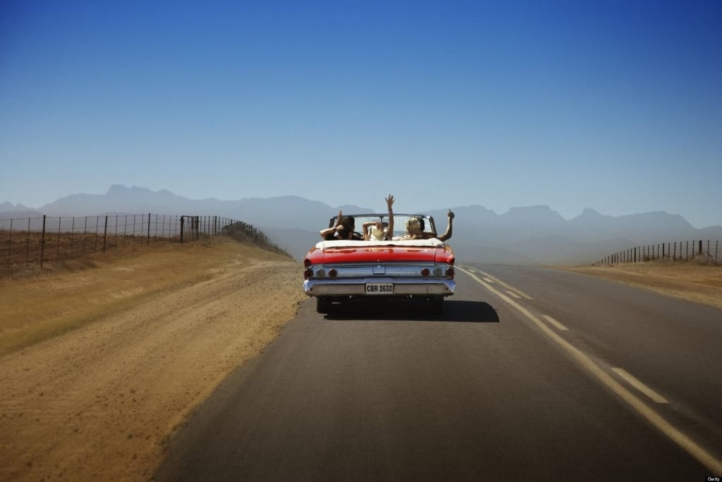 People on road trip riding in convertible car
